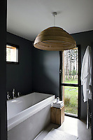 The walls of this contemporary bathroom have been painted a matt black while the floor-to-ceiling glass door frames a view of the surrounding landscape