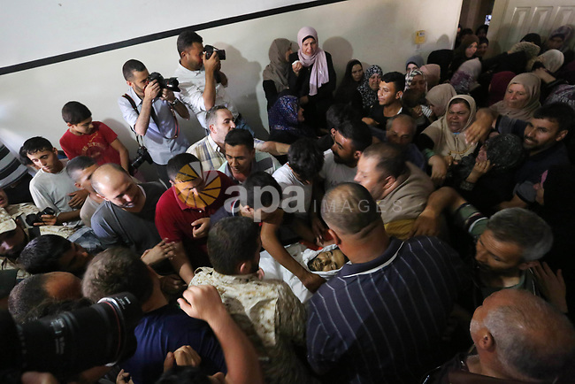 """Palestinian mourners carry the body of a Hamas security forces member, Mahmoud al-Adham, 28, into the family home during his funeral in Town of Jabaliya, northern Gaza Strip, Thursday, July 11, 2019. Hamas' armed wing said Thursday that the Israeli army """"deliberately"""" fired at al-Adham, in the northern town of Beit Hanoun. Photo by Ashraf Amra"""