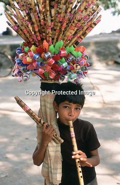 A small boy tries to sell whistles to visitors at the Chinese Fishing Nets in Cochin, India, and demonstrates their qualities by playing a tune.