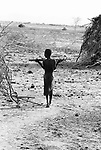 A Turkana child and automatic weapon in a traditional village nr Kakuma, Northern Kenya.<br /> His family may use the gun as protection against marauding tribes that come and steal their livestock.<br /> <br /> With the high amount of unrest in the region there has been a proliferaiton of weapons and a Kalashnikov can be  bought for as little as $10 USD.