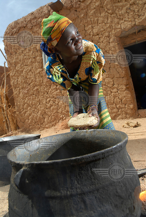 Nana Badama prepares a meal using a huge cooking pot outside her home in Dan Saga village.