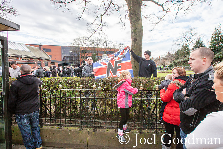 "© Joel Goodman - 07973 332324 . 03/03/2012 . Heywood , UK . Protesters hold up a National Front banner with a 14 words quote from David Lane , "" We must secure the existence of our people and a future for white children "" . The National Front hold a rally in protest against an alleged paedophile ring that had been operating in the area . There is currently (3rd March 2012) a case being tried at Liverpool Crown Court in relation to the allegations . Last Thursday (23rd February 2012) a protest organised in the town in relation to the same story resulted in Asian business being attacked by an angry mob . Photo credit : Joel Goodman"
