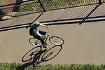 Man riding his bike on a sidewalk in Denver, Colorado. .  John offers private photo tours in Denver, Boulder and throughout Colorado. Year-round.