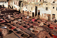 General view of Chouara tannery, Fez, Morocco, pictured on February 22, 2009 in the morning. The Chouara tannery is the largest of the four ancient tanneries in the Medina of Fez where the traditional work of the tanners has remained unchanged since the 14th century. It is composed of numerous dried-earth pits where raw skins are treated, pounded, scraped and dyed. Tanners work in vats filled with various coloured liquid dyes derived from plant sources. Colours change every two weeks, poppy flower for red, mint for green, indigo for blue, chedar tree for brown and saffron for yellow. Fez, Morocco's second largest city, and one of the four imperial cities, was founded in 789 by Idris I on the banks of the River Fez. The oldest university in the world is here and the city is still the Moroccan cultural and spiritual centre. Fez has three sectors: the oldest part, the walled city of Fes-el-Bali, houses Morocco's largest medina and is a UNESCO World Heritage Site;  Fes-el-Jedid was founded in 1244 as a new capital by the Merenid dynasty, and contains the Mellah, or Jewish quarter; Ville Nouvelle was built by the French who took over most of Morocco in 1912 and transferred the capital to Rabat. Picture by Manuel Cohen.
