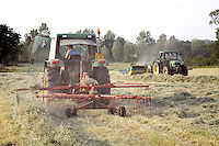 Farm worker raking hay into rows with tractor
