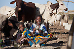 In the seasonal village of Bantagiri in northern Burkina Faso, a Fulani woman makes yarn which she will use to weave a straw mat.  The Fulani are traditionally nomadic pastoralists, crisscrossing the Sahel season after season in search of fresh water and green pastures for their cattle and other livestock.