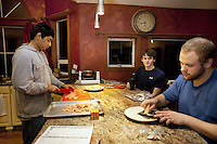USA. Washington state. Fall City. ReStart Internet Addiction Recovery program at Heavensfield Retreat Center. Dinner time. Shlok (L) and Kevin  (R) are preparing the food. Andrew (C) seta at the bar, drinks juice and talks to the cooks. Shlok is 22 years old and is a citizen from India. Andrew is 20, Kevin 22, both are american citizens. All three have dropped out of university because they were highly addictive online video gamers on internet. ReStart is an unique intensive onsite program which offers to participants an opportunity to stay in a retreat center designed to promote insight and renewal, disconnect from digital distractions, and engage in coaching and mentoring while building a blue print for change. The three to six-month reStart program, the first of this kind in the United States, works to help men over 18, suffering from problematic internet, video game, social media and technology use by teaching positive and sustainable lifestyle change in a serene, rural environment surrounded by nature. 9.12.2014 © 2014 Didier Ruef