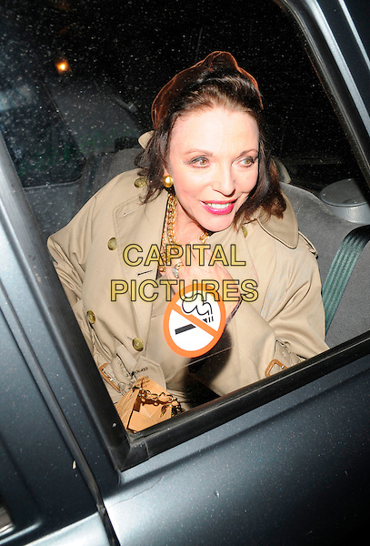JOAN COLLINS.At The Ivy Restaurant,.London, England, .April 5th 2008..half length beige trench coat gold necklaces sitting in car cab no smoking sign sticker on window .CAP/CAN.©Can Nguyen/Capital Pictures
