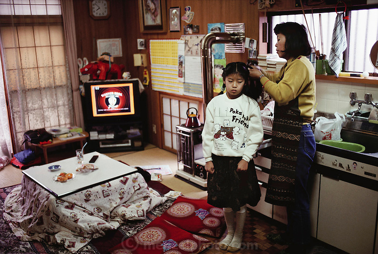 Mio Ukita has her hair brushed by her mother Sayo before school. Japan. Material World Project. The Ukita family lives in a 1421 square foot wooden frame house in a suburb northwest of Tokyo called Kodaira City.