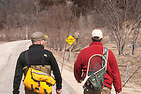 Anglers walk down a rural road while fly fishing in the Driftless Area of southwest Wisconsin.