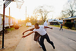 "Kevin ""Booma"" Williams (black shirt), 18, plays Ta Posey (white shirt), 18, in a game of street basketball on Kilpatrick Street in Greensboro, Alabama, February 28, 2013, where over a quarter of the population receives Social Security Disability benefits."