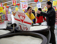 A shopper asks a store employee questions about rice on sale at a Carrefour Supermarket in Shanghai, China. According to a recent report, China has surpassed the United States in total consumption of every basic food, energy, and industrial commodity except oil, as well as goods such as television sets, refrigerators and mobile phones. However the per capita income for China is only roughly one seventh of that of the U.S..19 Feb 2005