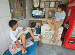 "In the capital of the Philippines, children watch television in their home in the Manila North Cemetery. Hundreds of poor families live in the cemetery, dwelling inside and between the tombs and mausoleums of the city's wealthy. They are often discriminated against, and many of their children don't go to school because they're too hungry to study and they're often called ""vampires"" by their classmates. With support from United Methodist Women, KKFI--a Filipino NGO--provides classroom education and meals to kids from the cemetery at a nearby church."