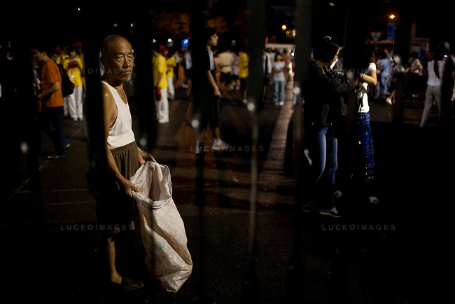 A man stands outside of Worker's Stadium asking for recyclable containers from fans in Beijing, China on Monday, August 18, 2008.  Kevin German