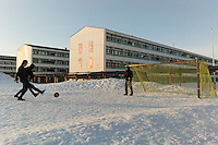 Nuuk, Greenland - Local kids play football on a snow covered pitch at a public housing estate in Nuuk, Greenland, March 2016. Nuuk is the capital and largest city of Greenland. It is the seat of government and the country's largest cultural and economic centre. The major cities closest to the capital are Iqaluit and St. John's in Canada and Reykjavík in Iceland. Nuuk contains almost a quarter of Greenland's population, and also has the tallest building in Greenland. Nuuk is the seat of government for the Sermersooq municipality. In January 2016, it had a population of 17,316.