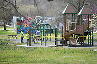 Fayetteville Parks and Recreation Department employees  tape off playground equipment and dismantle swing sets Tuesday March 24, 2020 at Walker Park. The city is shutting down all playgrounds, sports parks, restrooms, basketball courts and water fountains as a means to prevent the spread of covid-19. Visit nwaonline.com/200325Daily/ for more photos. (NWA Democrat-Gazette/J.T. Wampler)