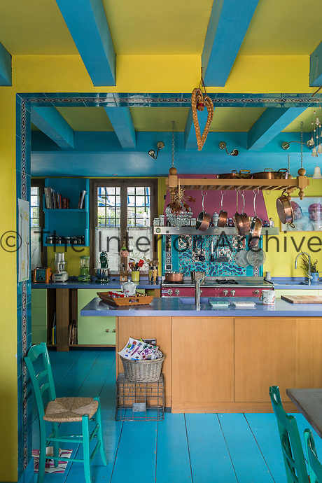 The kitchen continues the colourful painted decorative theme of other rooms in the house