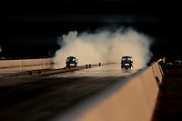 Sept. 17, 2010; Concord, NC, USA; A pair of NHRA pro mod cars do their burnout during qualifying for the O'Reilly Auto Parts NHRA Nationals at zMax Dragway. Mandatory Credit: Mark J. Rebilas/