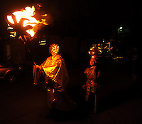 STAFF PHOTO ANDY SHUPE - Dan Barth of Springdale, dressed as the Fire Priest, left, carries a burning sun ahead of Sean Thorup, 11, of Fayetteville, dressed as the New Sun, during a celebration of the winter solstice Sunday, Dec. 21, 2014, at the Unitarian Universalist Fellowship of Fayetteville.
