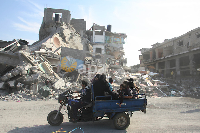 Palestinians ride a motorcycle past a damaged buildings following Israeli air strikes in Gaza city on November 20, 2012. The Israeli military said it attacked about 100 targets in the coastal strip during the night, using aircraft, warships and artillery. Photo by Eyad Al Baba