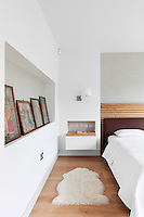 A modern white bedroom with a double bed with a leather headboard. A wall-mounted bedside table is set in a recess.
