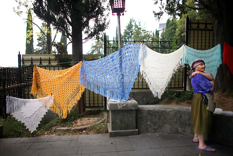 A woman sells hand-woven scarves and blankets for small change at the Black Sea resort Sochi, Russia on Wednesday, August 13, 2008. The government has pledged to invest $12 billion to transform the Soviet-era resort town into a Mediterranean-style retreat. <br /> <br /> As the mountainous Black Sea resort Sochi, Russia, prepares for the Winter Olympic games scheduled there for 2014, it emerges as a place replete with contradictions -- glitzy clubs and impoverished street vendors, progress and repression, Westernization and former Eastern bloc ideologies.