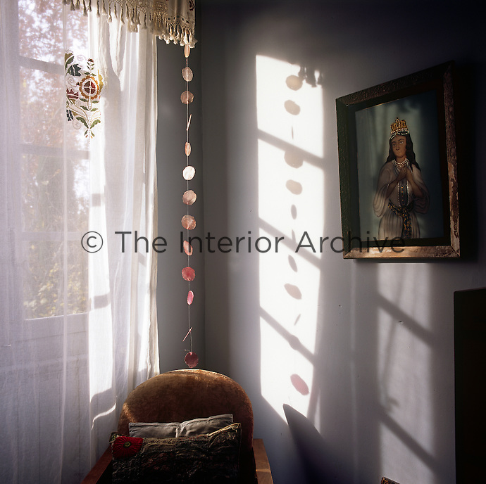 An armchair stands in the corner of a room next to a window dressed with a sheer curtain.