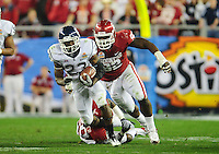 Jan. 1, 2011; Glendale, AZ, USA; Oklahoma Sooners defensive tackle (92) Stacy McGee attempts to tackle Connecticut Huskies tailback (23) Jordan Todman in the 2011 Fiesta Bowl at University of Phoenix Stadium. The Sooners defeated the Huskies 48-20. Mandatory Credit: Mark J. Rebilas-
