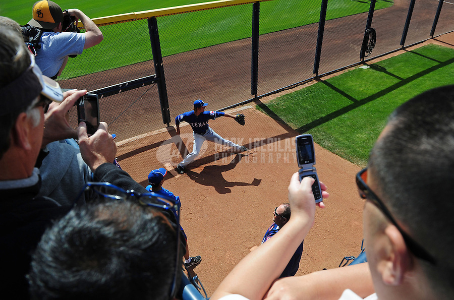 Mar. 7, 2012; Peoria, AZ, USA; Texas Fans take pictures as Rangers pitcher Yu Darvish warms up in the bullpen prior to the game against the San Diego Padres at Peoria Stadium.  Mandatory Credit: Mark J. Rebilas-.