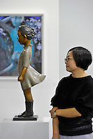 HONG KONG - MARCH 13:  An exhibitor stands next to sculpture 'No'' by Li Wei and Liu Zhiyin in art fair Art Central on its first day on March 13, 2015 in Hong Kong, Hong Kong.  (Photo by Lucas Schifres/Getty Images)