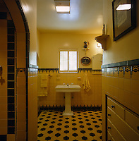 A wash basin on a pedestal stands beneath a small window in this tiled Art Deco bathroom