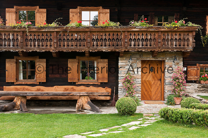 A spectacular length of wood balanced on a pair of tree trunks serves as an outdoor dining area at the entrance to the chalet