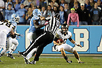 17 October 2015: Umpire Rich McMahan (U) is knocked over by UNC's Shakeel Rashad (42) as he pursues Wake Forest's John Wolford (10). The University of North Carolina Tar Heels hosted the Wake Foresst University Demon Deacons at Kenan Memorial Stadium in Chapel Hill, North Carolina in a 2015 NCAA Division I College Football game.