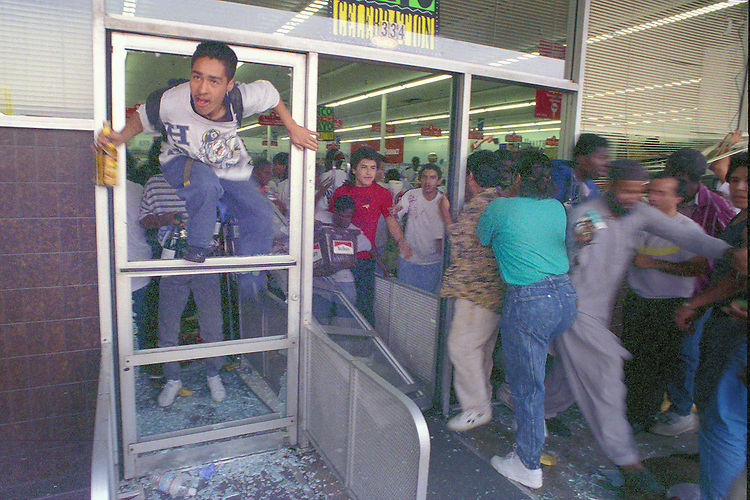 """A man jumps through the broken door of a shop holding a tequila bottle while other looters push through the breeched entry during the """"uprising"""" of rioting and looting in the Koreatown neighborhood of Los Angeles, Calif. following the acquittal of LAPD officers accused of beating motorist Rodney King, May 30, 1992. Los Angeles suffered city wide chaos and destruction following the the end of the first trial against accused officers Sergeant Stacey Koon, Laurance Powell, Theodore Briseno and Timothy Wind. A later  Federal Civil Rights Trial sent officers Powell and Koon to prison for 30 months while Briseno and Wind were acquitted. Photo copyright Gerard Burkhart 818-207-0273)"""