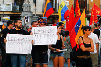 "Demonstrators  supports President Maduro holds a poster entitle ""Ledezma and Leopoldo assasins""."