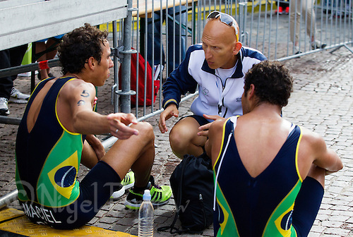 25 AUG 2012 - STOCKHOLM, SWE - Paulo Roberto Maciel (BRA) (left) of Brazil and Rafael Fonseca (BRA) (right), also of Brazil, talk with coach Sergio Santos (centre) after finishing the men's 2012 ITU World Triathlon Series round in Gamla Stan, Stockholm, Sweden .(PHOTO (C) 2012 NIGEL FARROW)