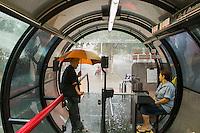 CURITIBA, PR, 04.02.2014 – CLIMA TEMPO /CURITIBA -  Depois de uma semana com temperatura acima de 30º C, choveu na tarde dessa terça-feira(04), em Curitiba. Passageira aguarda a passagem da chuva no ponto de ônibus. (FOTO: PAULO LISBOA  / BRAZIL PHOTO PRESS)