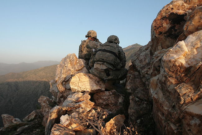 Two soldiers from Company A,  2nd Battalion, 503rd Parachute Infantry Regiment, look for Taliban fighters from atop a mountain in the Narang valley, in Kunar Province, Afghanistan. The soldiers were protecting a team during the two-day mission that directed air and artillery strikes on Taliban positions in the valley below. <br /> May 17, 2008. DREW BROWN/STARS AND STRIPES