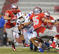STAFF PHOTO ANDY SHUPE - Midland Christian quarterback Gary Powell (5) breaks free from Highland defensive back Preston Gurley (15) during the first half of play Monday, Sept. 1, 2014, at Razorback Stadium in Fayetteville.