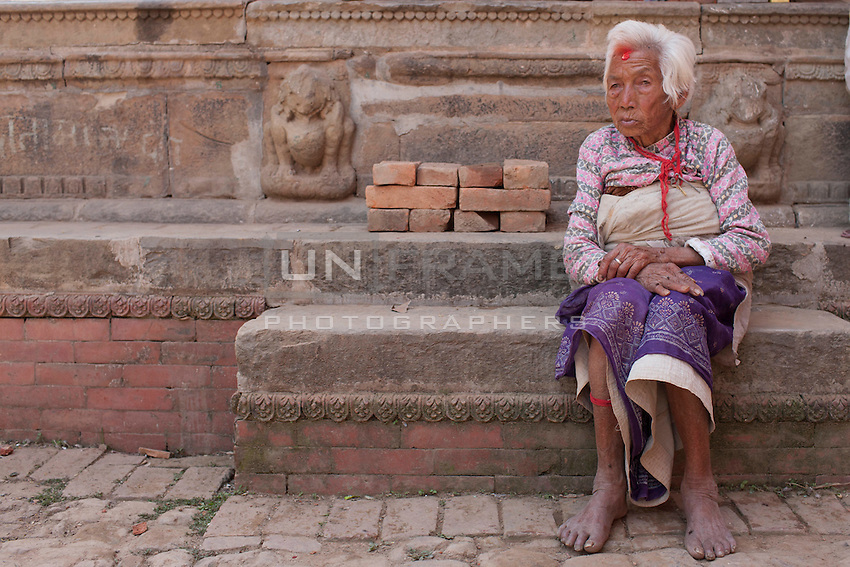 A woman sits in front of her destroyed house at Changu village,  Bhaktapur, outside of Kathmandu, Nepal. May 05, 2015