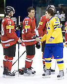 Dominik Schlumpf (Switzerland - 18), Nino Niederreiter (Switzerland - 22), Anton Lander (Sweden - 16) - Team Sweden celebrates after defeating Team Switzerland 11-4 to win the bronze medal in the 2010 World Juniors tournament on Tuesday, January 5, 2010, at the Credit Union Centre in Saskatoon, Saskatchewan.