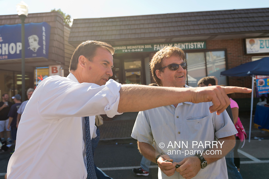 Bellmore, New York, U.S. 22nd September 2013. Former Nassau County Executive TOM SUOZZI (Democrat), who is running for his former office again, points to something while talking with a man, during Suozzi's campaign stop to the 27th Annual Bellmore Family Street Festival, featuring family fun with exhibits and attractions in a 25 square block area, with over 120,000 people expected to attend over the weekend.