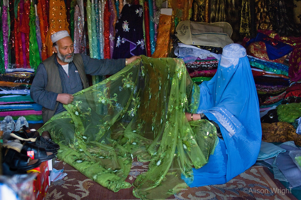 Women in burkas shopping for material in the market.