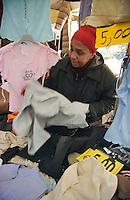 Milano, mercato rionale di viale Papiniano. Venditrice di abiti --- Milan, local market in Papiniano street. Seller of clothes