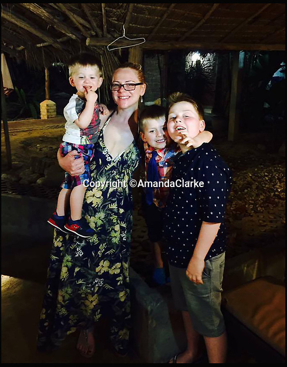 BNPS.co.uk (01202 558833)<br /> Pic: AmandaClarke/BNPS<br /> <br /> Amanda with her kids Charlie, Tobias and Oliver on holiday in Thailand just before the accident.<br /> <br /> A mum-of-three is lucky to be alive after her top turned into a fireball while she was cooking dinner for her family.<br /> <br /> Amanda Clarke was left with third degree burns that need a skin graft when her polyester top caught on the gas hob and engulfed her in flames.<br /> <br /> The 34-year-old was forced to rip the top like wrestler Hulk Hogan to get it off over her head, burning her eyeballs and singeing her hair in the process.<br /> <br /> She is now recovering in hospital but will be left with permanent scars to her right arm and chest.