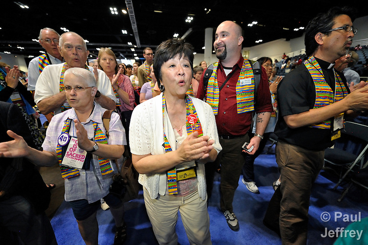 Protestors take over the floor at the end of a May 2 session of the 2012 United Methodist General Conference in Tampa, Florida. They expressed concern that the church's decisions on restructure, ending guaranteed clergy appointments, human sexuality, and corporate divestment were made without hearing the voice of youth and others in the church. The protestors sang and chanted as the presiding bishop gave a closing prayer.