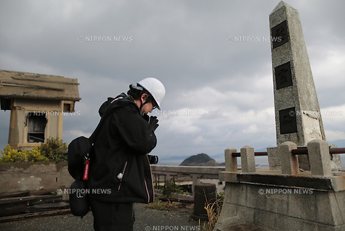 "In this December 11, 2013 photo,  director Shinji Higuchi fold his hands together in front of a memorial monument during a location hunting for his film, ""Attack on Titan"" on Hashima Island, commonly known as Gunkanjima, which means ""Battleship Island"" off Nagasaki, Nagasaki Prefecture, southern Japan. (Photo by Yuriko Nakao/AFLO) (No Third Party Sales, Minimum $50.00 Per Image)"