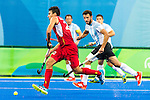 Simon Gougnard #22 of Belgium carries the ball while covered by Manuel Brunet #24 of Argentina during Argentina vs Belgium  in the men's gold medal game at the Rio 2016 Olympics at the Olympic Hockey Centre in Rio de Janeiro, Brazil.