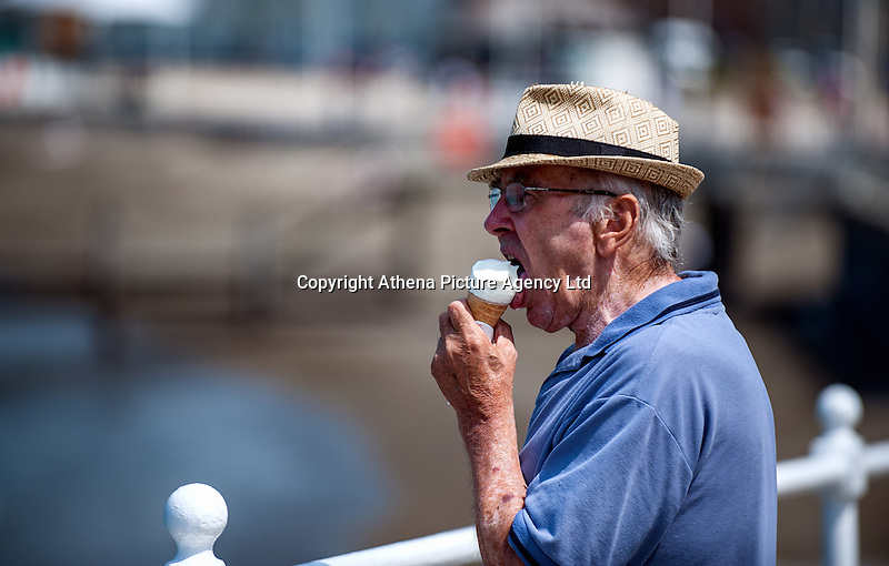 HOT WEATHER WALES Aberystwyth, Ceredigion, West Wales. UK Weather Wednesday  8th June 2016: With yellow warnings for rain across swathes of England the sun comes out at lunchtime with temperatures reaching 19 degrees celsius after a dull morning. A man enjoys an ice cream on his walk along the prom.