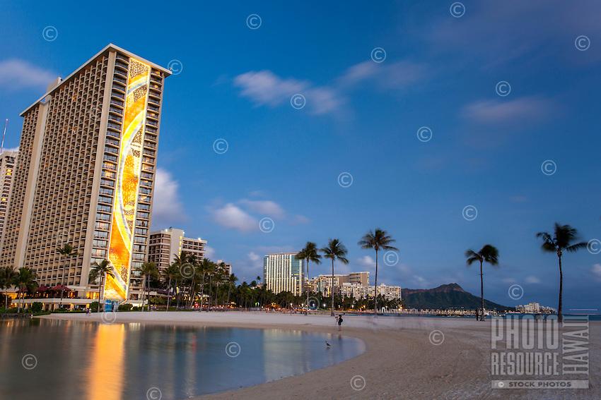 At dusk, the Hilton's Rainbow Tower is reflected in the Duke Kahanamoku Lagoon, Waikiki, O'ahu.